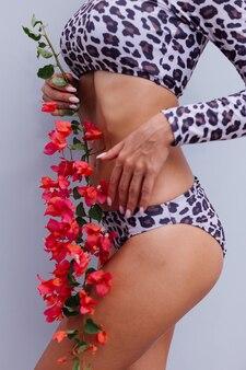 Sprawna kobieta w bikini lamparta, trzymając kwiaty