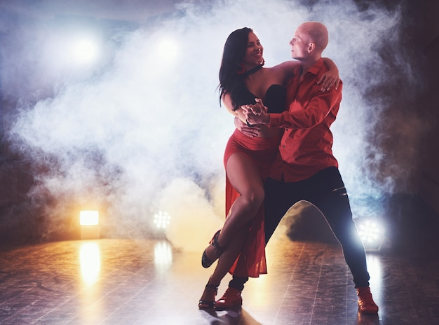 Sprawni tancerze występujący w ciemnym pokoju pod koncertowym światłem i dymem. zmysłowa para wykonująca artystyczny i emocjonalny taniec współczesny