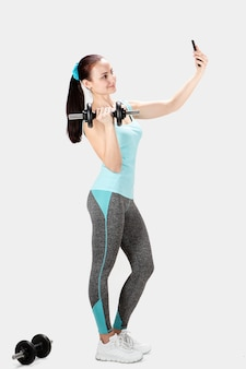 Sprawność fizyczna bawi się kobiety mienia dumbbell i brać selfie