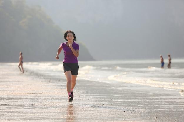 Sprawność fizyczna biegacza kobieta na ao nang plaży, krabi, tajlandia