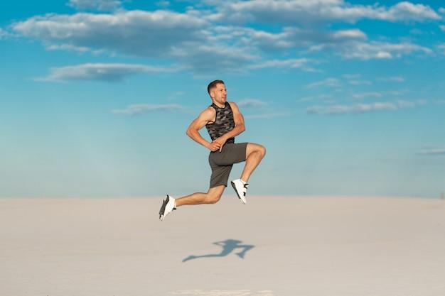 Sprawność fizyczna mężczyzna robi ćwiczeniom w piasek pustyni. koncepcja sportu
