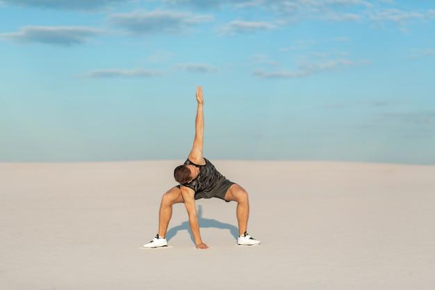 Sprawność fizyczna mężczyzna robi ćwiczeniom w piasek pustyni, sporta pojęcie