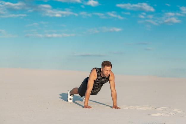 Sprawność fizyczna mężczyzna robi ćwiczeniom w piasek pustyni.