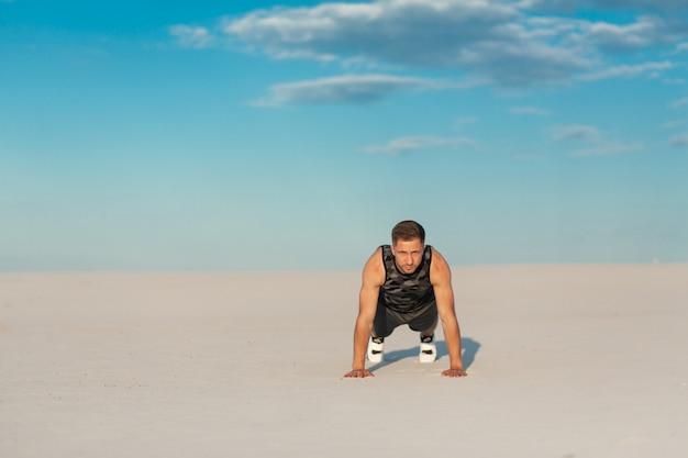 Sprawność fizyczna mężczyzna robi ćwiczeniom w piasek pustyni