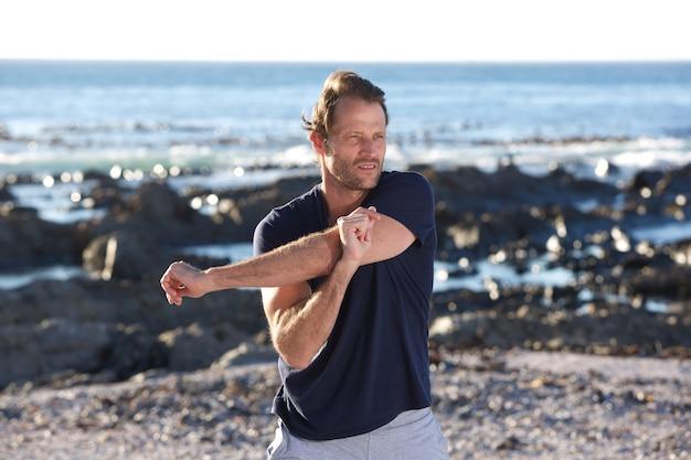 Sprawność fizyczna mężczyzna rozciąga outdoors morzem