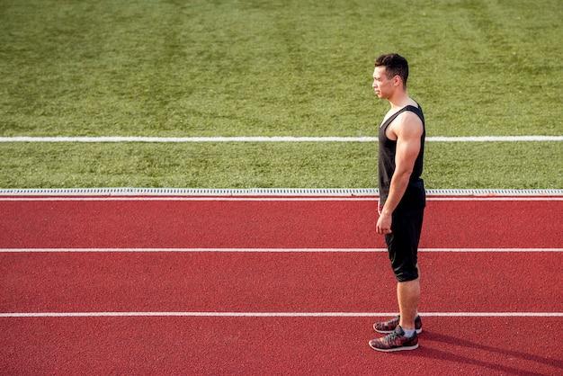 Sprawność fizyczna młoda męska biegacz pozycja na czerwonym bieg śladzie