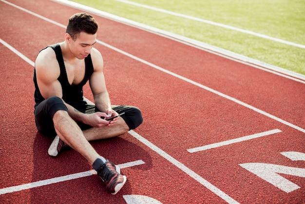 Sprawność fizyczna młody człowiek używa telefon komórkowego podczas gdy siedzący na biegowym śladzie