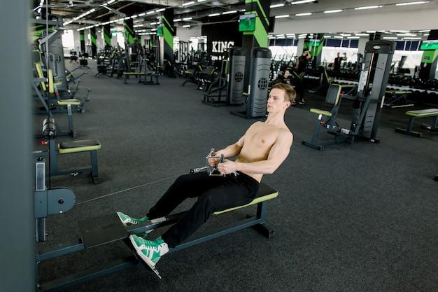 Sprawność fizyczna młody człowiek używa wioślarską maszynę w gym. sportowy mężczyzna na siłowni