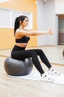 Sprawność fizyczna, pięknej kobiety uśmiechnięta twarz cieszy się trening z dysponowaną piłką w sprawności fizycznej - sporta i stylu życia pojęcie.