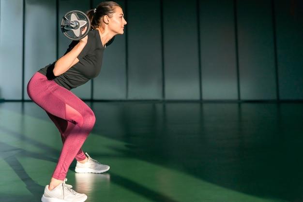 Sprawność fizyczna, sport, trójbój siłowy i ludzie pojęć, - sporty kobieta ćwiczy z barbell w gym