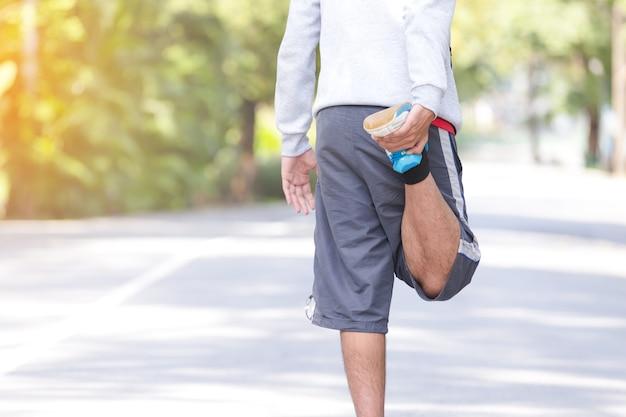 Sprawność fizyczna sporta młodego człowieka biegacz robi rozciągania ćwiczeniu w parku koncepcja zdrowego