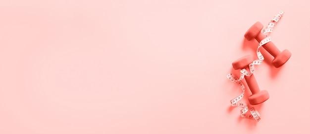 Sprawność fizyczna, sporta pojęcie z dumbbells i pomiarowa taśma nad koralowym koloru tłem.