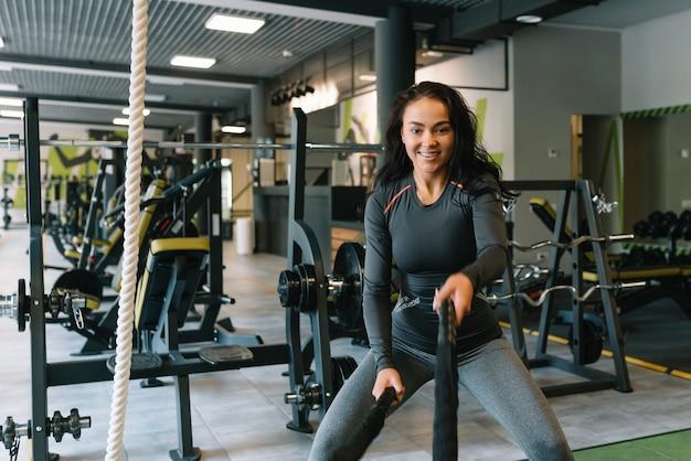 Sprawność na linach. piękna kobieta w siłowni, ćwicząc z liny. młoda kobieta ciężko trenuje.
