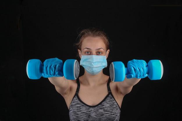 Sprawność podczas kwarantanny po pandemii covid-19. kobieta lekkoatletycznego w masce medycznej i rękawiczkach trzyma hantle w dłoniach na czarnej ścianie.