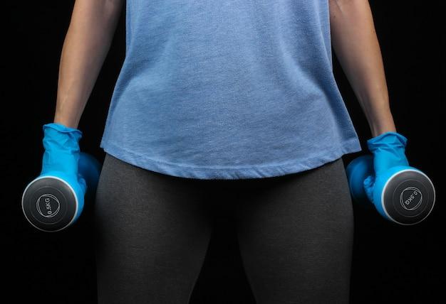 Sprawność podczas kwarantanny po pandemii covid-19. kobieta lekkoatletycznego w rękawiczkach trzyma hantle w dłoniach na czarnej ścianie.