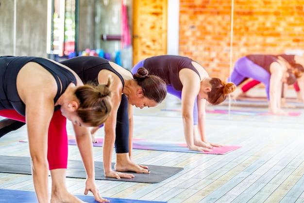 Sprawności fizycznej azjatykcia żeńska grupa robi rozgrzewkowej joga pozie w rzędzie przy joga klasą.
