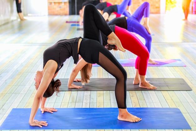 Sprawności fizycznej azjatykcia żeńska grupa robi rozgrzewkowej joga pozie