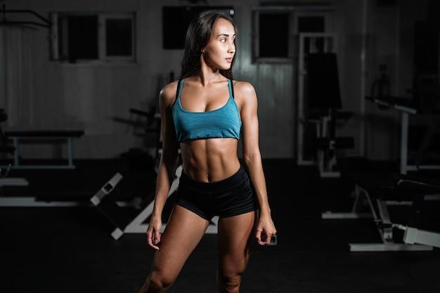Sprawności fizycznej dziewczyna ćwiczy z barbell, kobieta pozuje w gym