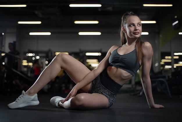 Sprawności fizycznej dziewczyna pozuje w gym obsiadaniu na podłoga pokazuje daleko jej ciało