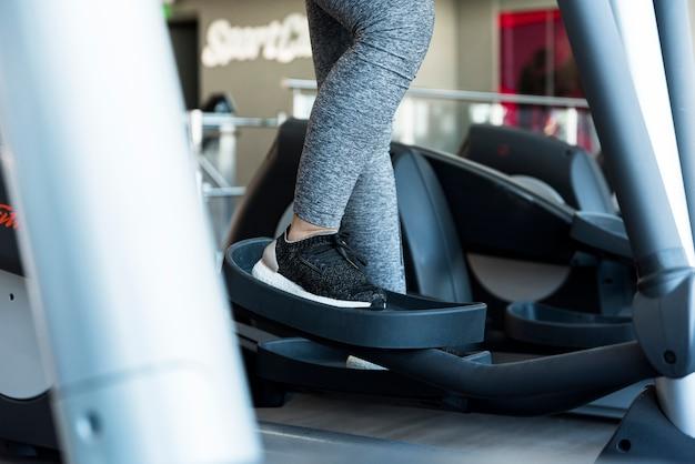 Sprawności fizycznej dziewczyna używa elliptical trenera