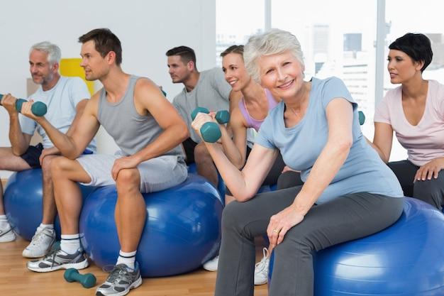 Sprawności fizycznej klasa z dumbbells siedzi na ćwiczenie piłkach w gym