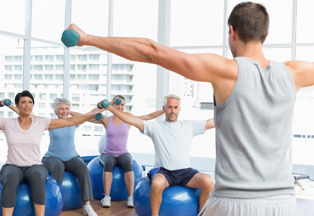 Sprawności fizycznej klasa z dumbbells siedzi na ćwiczenie piłkach