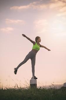 Sprawności fizycznej kobieta ćwiczy przy zmierzchu czasem,