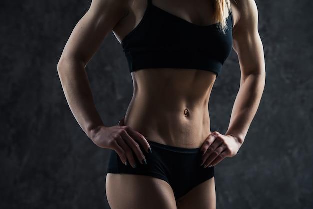 Sprawności fizycznej kobieta na ciemnej ścianie