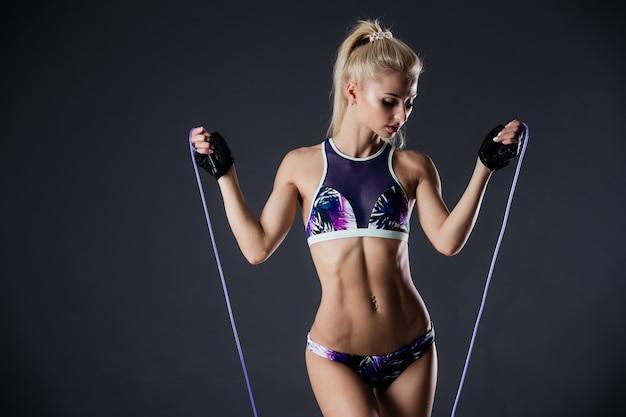 Sprawności fizycznej kobieta pozuje z omijać arkanę na czarnym tle. motywacja sportowa. idealna figura kobieca.
