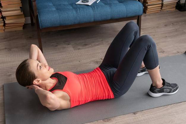 Sprawności fizycznej kobieta robi abs chrupnięcia treningowi na podłoga w domu