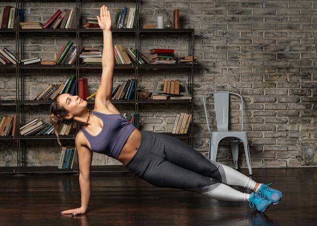 Sprawności fizycznej kobieta robi bocznej desce podczas joga treningu w domu
