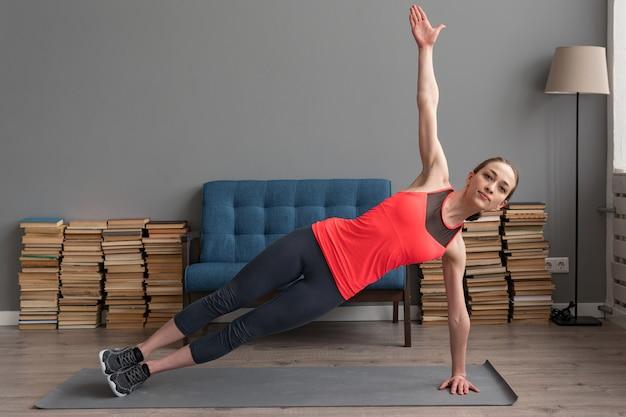 Sprawności fizycznej kobieta robi bocznej deski ćwiczeniu na macie w domu