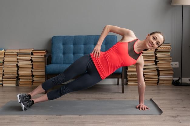 Sprawności fizycznej kobieta robi bocznemu deska treningowi na macie w domu