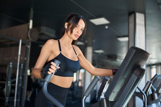 Sprawności fizycznej kobieta robi cardio w gym.