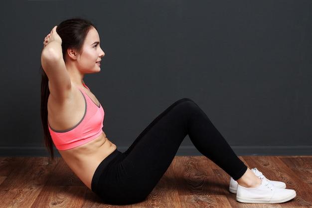 Sprawności fizycznej kobieta robi ćwiczeniom dla abs