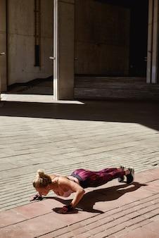 Sprawności fizycznej kobieta robi pcha podnosi plenerowego stażowego treningu lata wieczór bocznego widok
