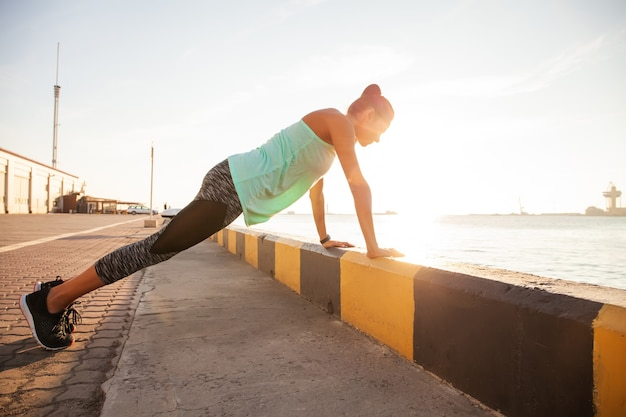 Sprawności fizycznej kobieta robi push up plenerowy trening treningowy letni wieczór widok z boku. pojęcie sportu zdrowego stylu życia