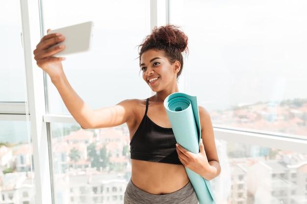 Sprawności fizycznej kobieta robi selfie na smartphone i ono uśmiecha się