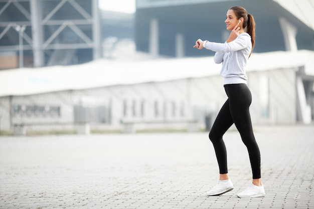 Sprawności fizycznej kobieta robi trening pozyci w stadium tle