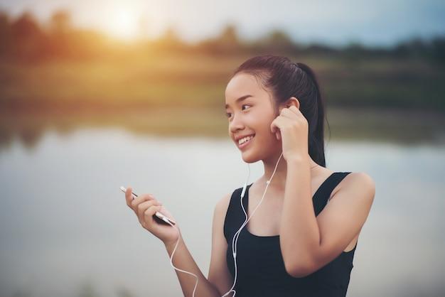 Sprawności fizycznej kobieta słucha muzykę podczas jej treningu i ćwiczenia w parku w słuchawkach