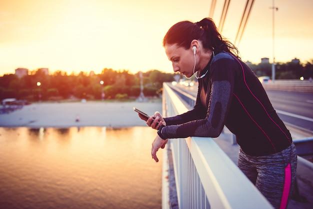 Sprawności fizycznej kobieta używa mądrze telefon