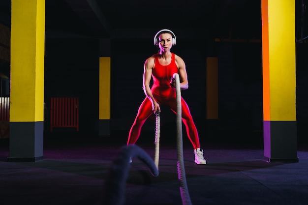 Sprawności fizycznej kobieta używa stażowe arkany dla ćwiczenia przy gym. atleta pracująca z batalistycznymi arkanami przy przecinającym gym