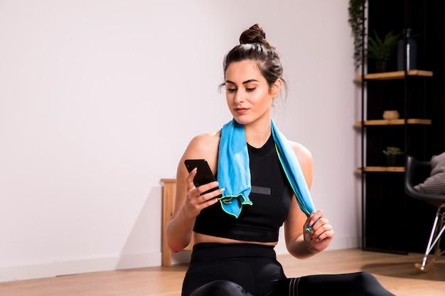 Sprawności fizycznej kobieta używa telefon komórkowego