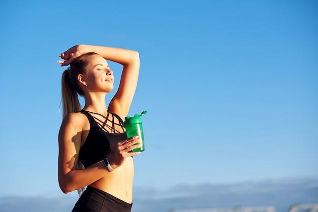 Sprawności fizycznej kobieta z butelką woda po biegać trenować na niebieskiego nieba tle