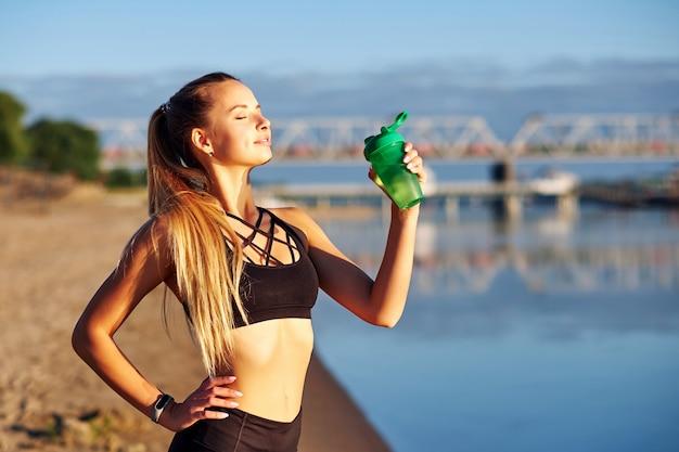 Sprawności fizycznej kobieta z butelką woda po biegać trenować na plaży wybrzeżu i ranku miastowym miasta tle