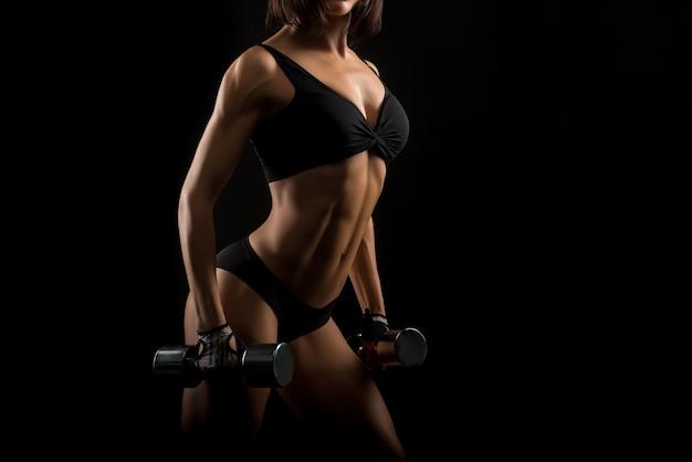 Sprawności fizycznej kobieta z perfect ciała mienia dumbbells