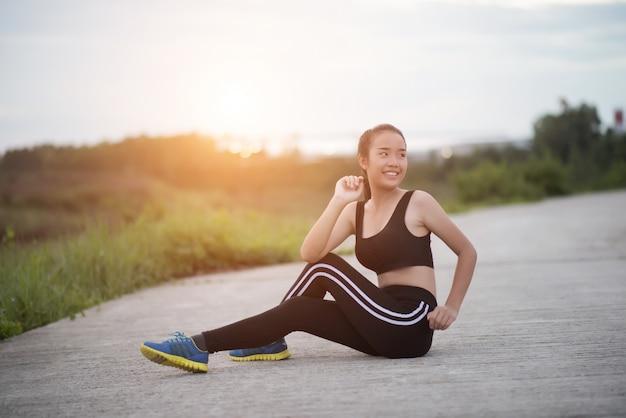 Sprawności fizycznej kobiety biegacz siedzi w dół relaksować z bidonem po trenować outside w parku