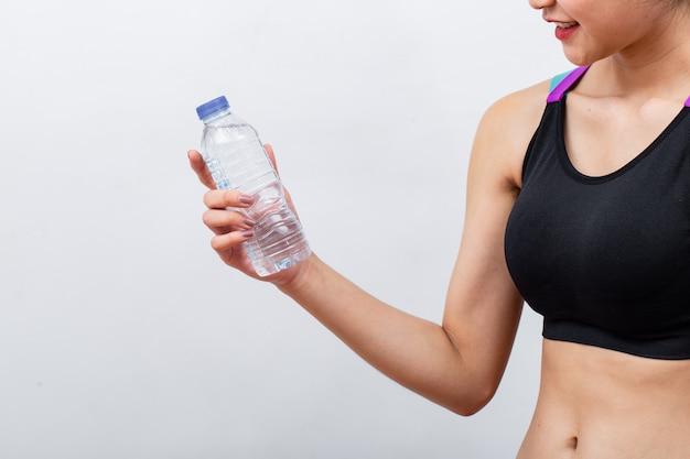 Sprawności fizycznej kobiety podnosi butelkę wodę i trzyma