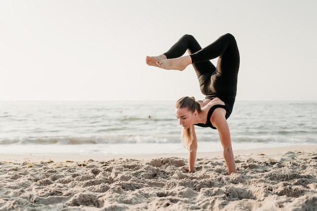 Sprawności fizycznej kobiety praktyki joga handstand asana na plaży blisko oceanu