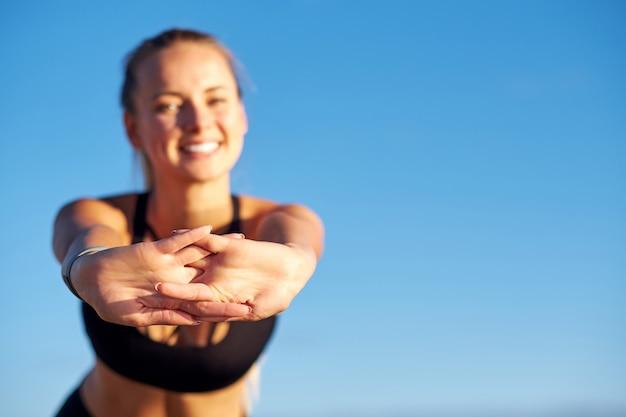 Sprawności fizycznej kobiety rozciągania ręki na niebieskiego nieba tle. po biegu wykonuje ćwiczenia. pojęcie zdrowego stylu życia.